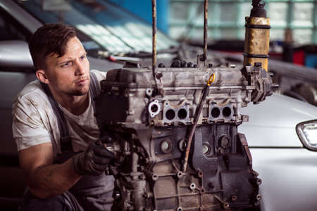 Photo pour Photo of professional auto technican diagnosing engine problem - image libre de droit