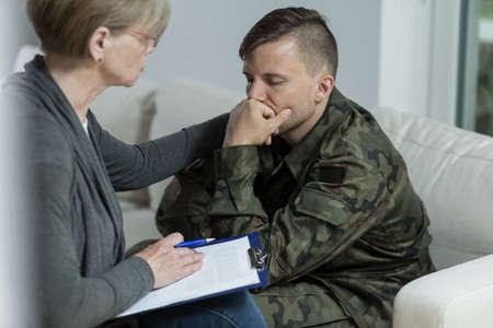 Foto de Image of mature psychologist and despair soldier - Imagen libre de derechos