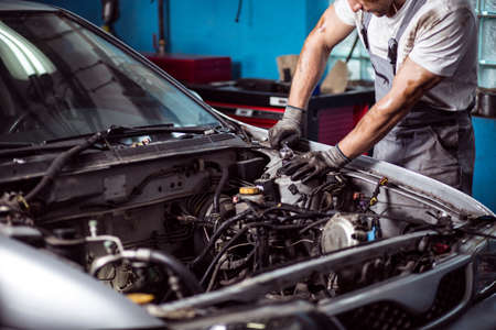 Photo pour Picture of uniformed auto mechanic maintaining car engine - image libre de droit
