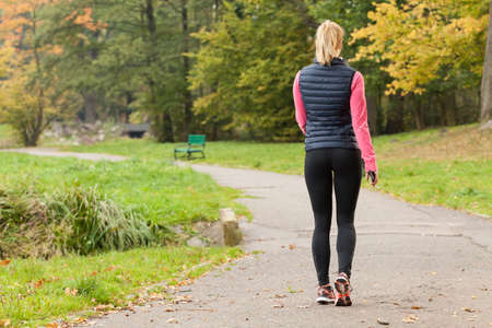 Foto de Fit woman walking in park during autumn time - Imagen libre de derechos
