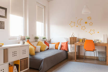 Photo pour Yellow and orange accessories in modern teen room - image libre de droit