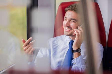 Photo for Picture of businessman in train making deal by phone call - Royalty Free Image