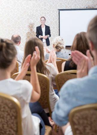 Photo pour Photo of audience applauding female professor after lecture - image libre de droit