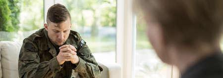 Foto de Young war soldier with emotional problems visiting a shrink - Imagen libre de derechos