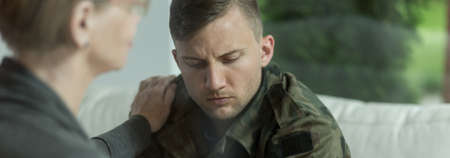 Foto de Psychologist comforting and supporting young soldier with trauma - Imagen libre de derechos