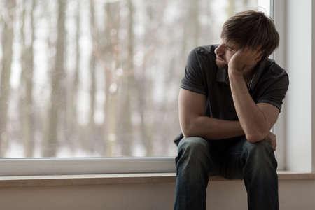 Foto de Young miserable depressed man sitting and thinking - Imagen libre de derechos