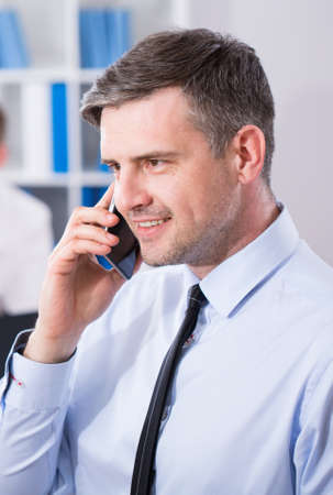 Photo for Office employer is talking on the mobile phone - Royalty Free Image