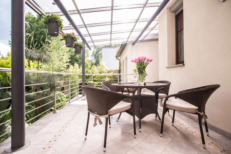 Photo pour Photo of neat rattan chairs and table standing on terrace - image libre de droit