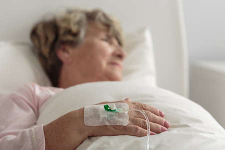 Photo for Ill female retiree lying in hospital bed - Royalty Free Image