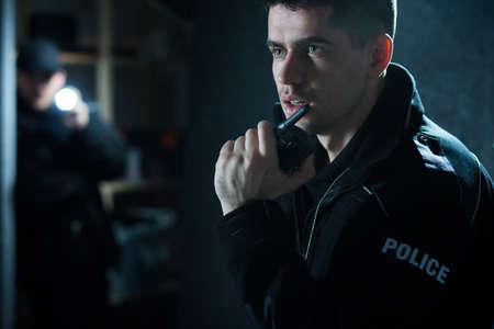Foto de Policeman at action talking on walkie talkie - Imagen libre de derechos