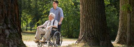 Foto de Young man is helping his grandfather in the park - Imagen libre de derechos