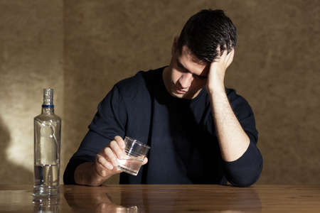 Photo pour Young man drinking vodka in the glass - image libre de droit