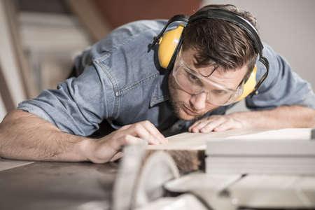 Photo pour Focused carpenter at work with wooden plank - image libre de droit