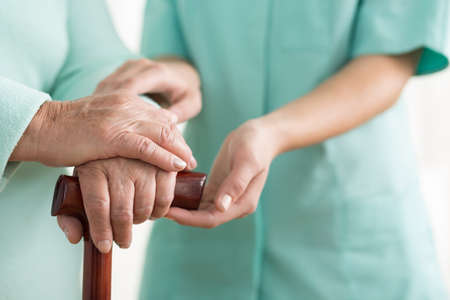Photo for Close-up of woman using cane assisted by physiotherapist - Royalty Free Image