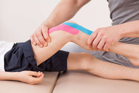 Photo for Close up of small boy with kinesio tape doing exercises - Royalty Free Image