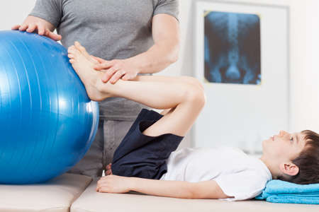 Photo for Picture of small patient doing exercises with fitness ball - Royalty Free Image