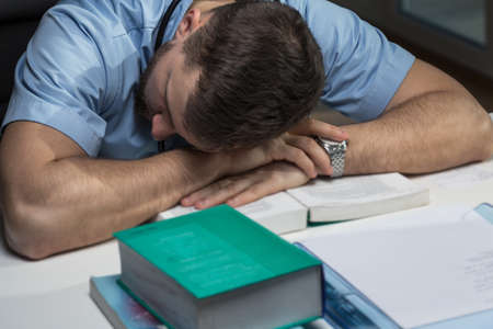 Photo pour Picture of very tired male doctor sleeping on desk - image libre de droit