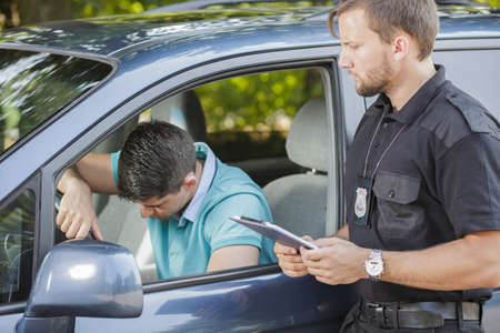 Photo pour Broken down young driver stopped by police officer - image libre de droit