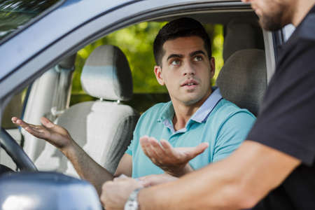 Photo pour Confused young man in the car stopped by policeman - image libre de droit