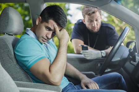 Photo for Worried young driver caught on driving after alcohol - Royalty Free Image