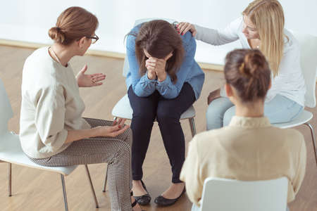 Photo pour Young despair woman crying during group therapy - image libre de droit