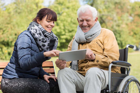 Foto de Smiling disabled man and caregiver with a tablet - Imagen libre de derechos