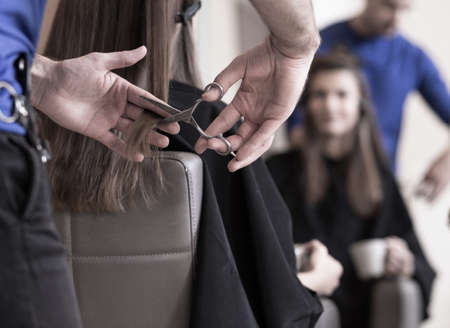 Photo pour Hairdresser is cutting young woman's hair - image libre de droit