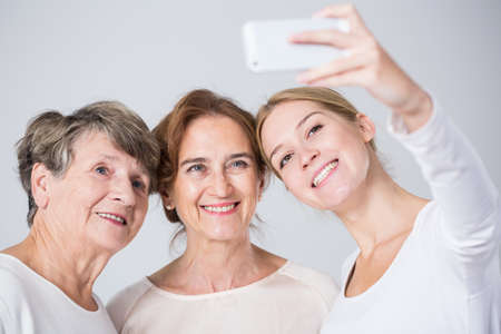 Photo pour Smiling granddaughter taking perfect family selfie - horizontal view - image libre de droit