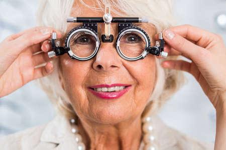 Foto de Senior woman in optician's office having examined sight - Imagen libre de derechos