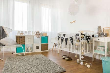 Photo pour Image of spacious infant bedroom with white furniture - image libre de droit