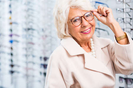 Foto de Elderly woman choosing reading glasses in optical shop - Imagen libre de derechos