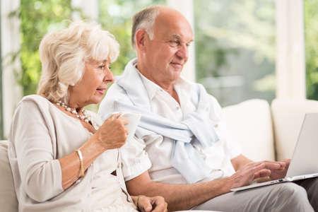 Foto de Image of modern elderly married couple using laptop - Imagen libre de derechos