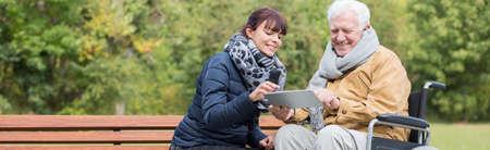 Foto de Smiling wheelchair man is using tablet outdoor - Imagen libre de derechos