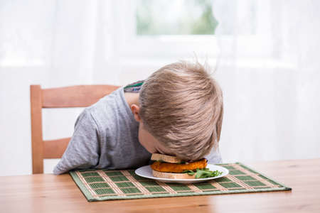 Photo pour Boy falling asleep and landing face in food - image libre de droit