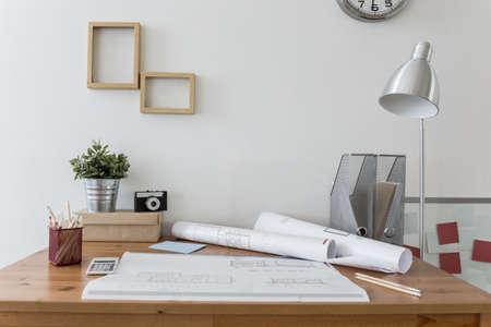 Photo pour Messy desk with architect's plans on it - image libre de droit