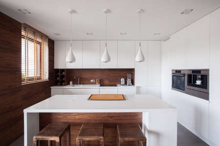 Photo pour White kitchen island in modern and wooden kitchen - image libre de droit