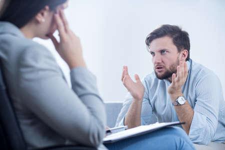 Foto de Angry man talking with psychiatrist or psychologist - Imagen libre de derechos