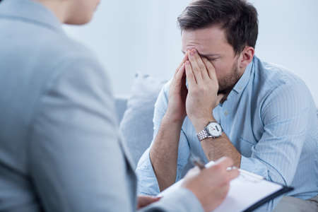 Foto de Man with depression crying during psychotherapy session - Imagen libre de derechos