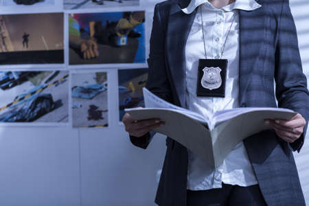 Foto de Police woman is reviewing files and documents - Imagen libre de derechos