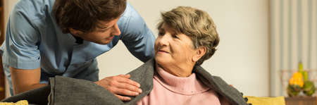 Photo pour Male helpful caregiver taking care of senior woman - image libre de droit