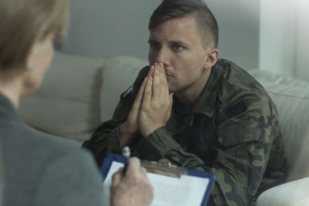 Photo pour Photo of depressed soldier on consultation with psychoanalyst - image libre de droit