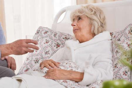 Foto de Ill senior woman lying in bed and resting - Imagen libre de derechos