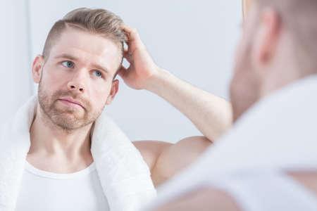 Foto de Young handsome guy looking at the mirror - Imagen libre de derechos