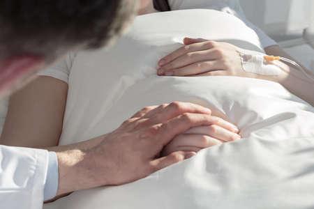 Foto de Close up of oncologist holding hand of girl with leukemia - Imagen libre de derechos