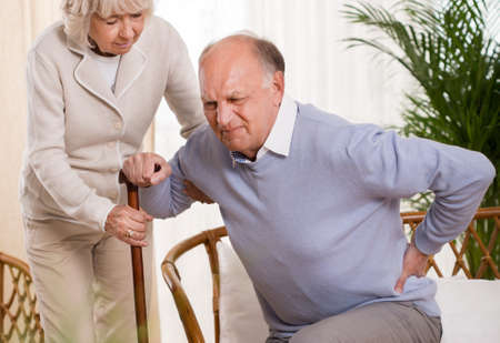 Photo for Woman helping an elderly man having a back pain - Royalty Free Image