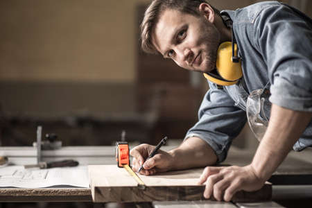 Foto de Photo of handsome carpenter measuring wooden board - Imagen libre de derechos