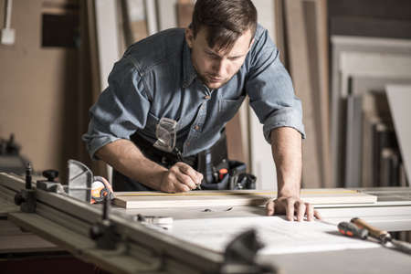 Photo pour Picture of handsome woodworker working on professional solid workbench - image libre de droit