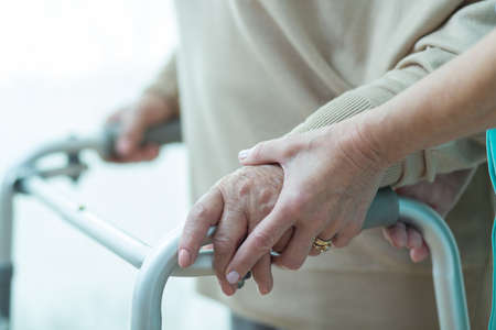 Photo for Close-up of woman using walker assisted by carer - Royalty Free Image