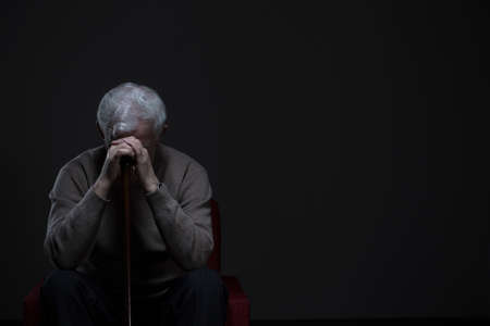 Foto de Depressed old man hiding his face behind hands - Imagen libre de derechos