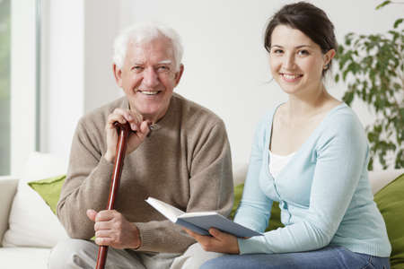 Photo pour Old man holding cane and young woman reading a book - image libre de droit